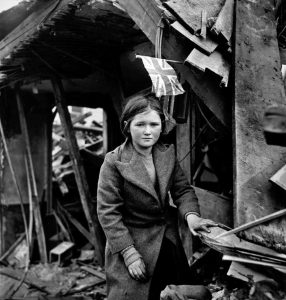 Toni Frissell - Battersea incident, England, January 1945 girl among the ruins, British flag overhead. Corresponds to V2 rocket bombing of Battersea, in London, of 27 January 1945